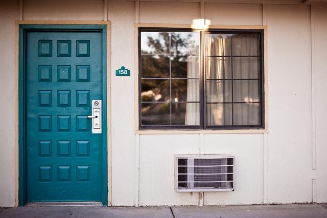 Biely rodinný dom s veľkým oknom a tyrkysovými vchodovými dverami