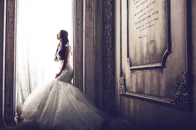 Nevesta vo svadobných šatách pozerá von cez veľké okno