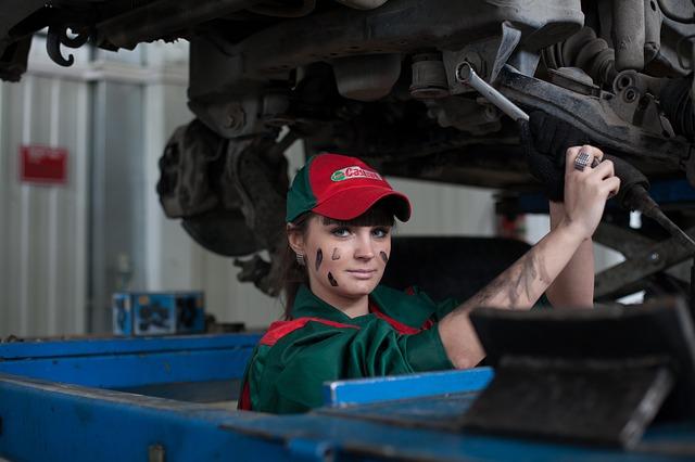 Žena v zelených monterkách, špinavou tvárou od oleja opravuje auto
