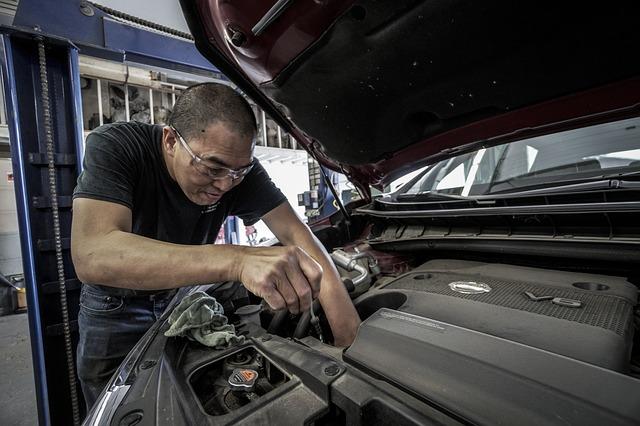 Muž opravuje auto s otvorenou kapotou