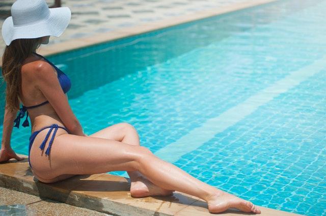 Žena v modrých plavkách sedí s vystretými nohami pri bazéne