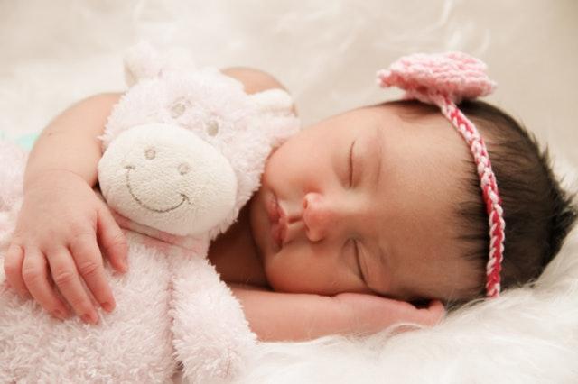 Bábätko s čelenkou na hlave spí s ružovou plyšovou hračkou