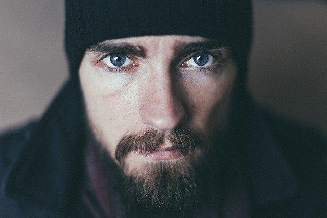 Muž s modrými očami, čiernou bradou a čiapkou na hlave.jpg