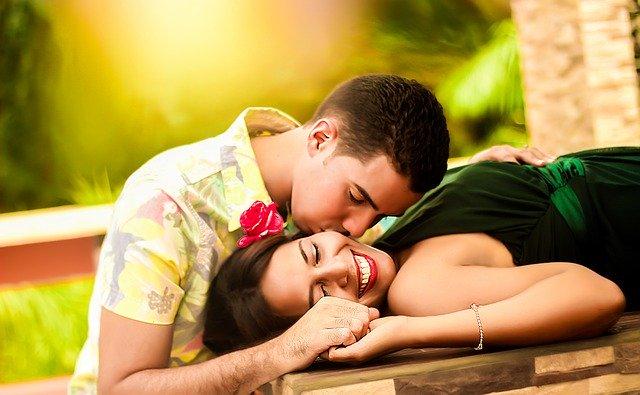 Muž vo farebnej košeli bozkáva ženu, ktorá leží na stole.jpg