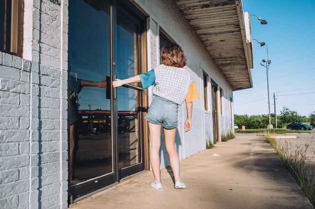 Žena otvára dvojkrídlové sklenené dvere.jpg
