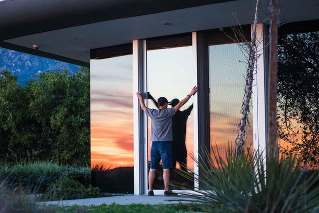 Muž stojí pri veľkých posuvných sklenených dverách.jpg