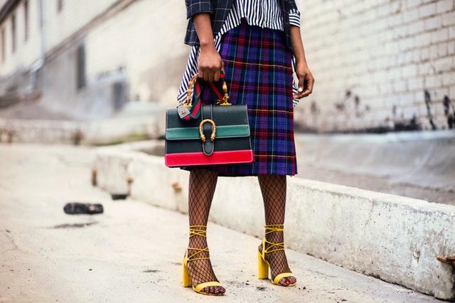 Žena v károvanej sukni, sieťkovaných pančuchách, žltých topánkach s farebnou kabelkou.jpg
