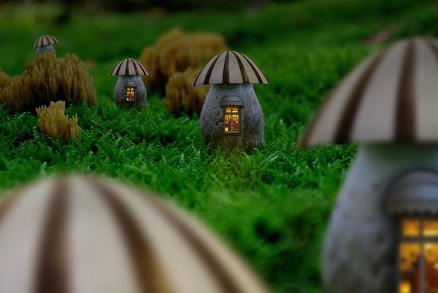 Malé domčeky v tvare húb so zapáleným svetlom v oknách rozložená na tráve.jpg