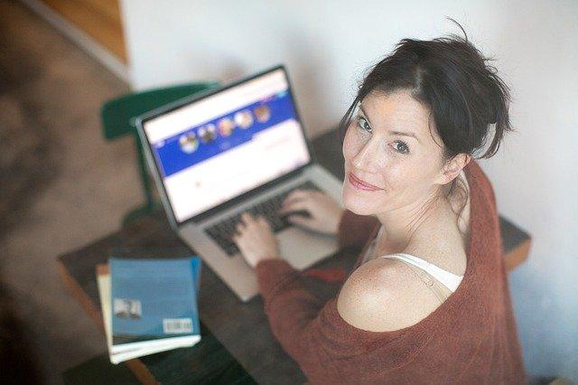 Žena v svetri sedí pro stole, usmieva sa a pracuje na počítači
